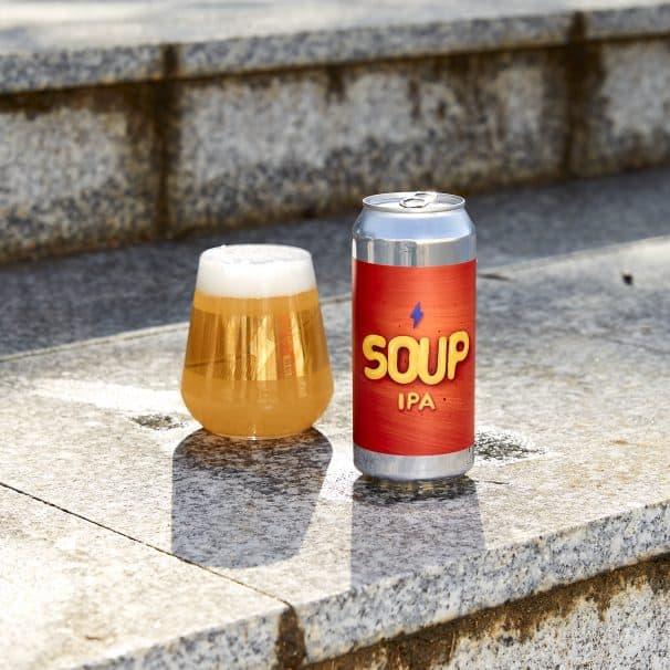Lata de soup IPA junto a un vaso de edición limitada